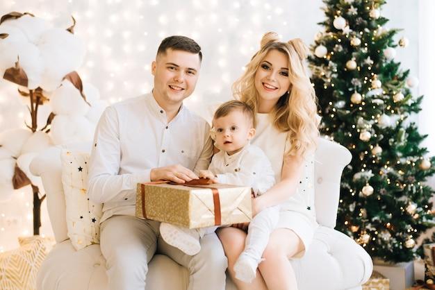 Jong gezin in de buurt van de kerstboom