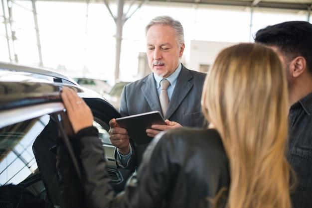 Jong gezin in gesprek met de verkoper en het kiezen van hun nieuwe auto in een showroom