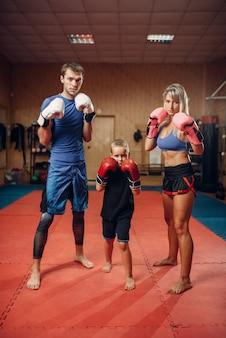 Jong gezin in handschoenen op kickbokstraining, sportschool interieur. paar en kleine jongen op zelfverdedigingstraining, martial arts oefenen