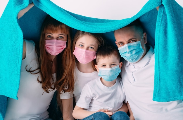 Jong gezin in medische maskers tijdens quarantaine thuis.