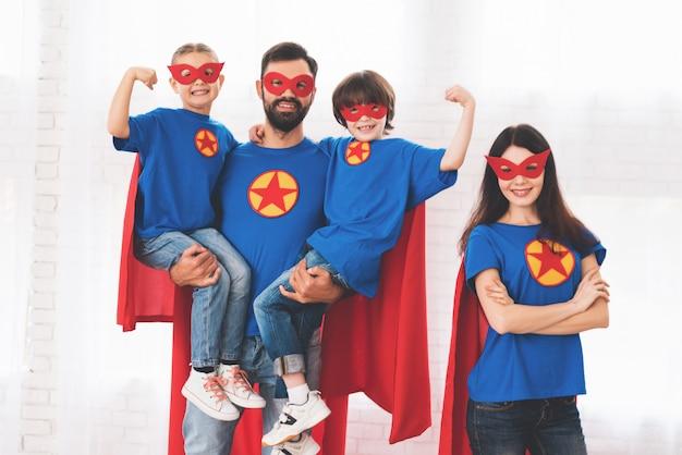Jong gezin in rode en blauwe pakken superhelden.