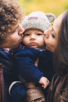 Jong gezin knuffelen in de herfst in park vader en moeder kussen zoontje op de wangen
