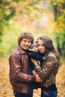 Jong gezin knuffelen in de herfst in park
