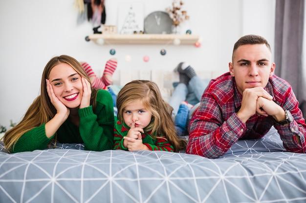 Jong gezin liggend op bed