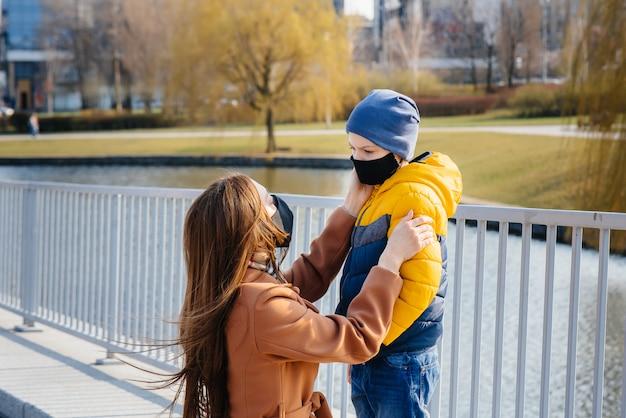 Jong gezin loopt en ademt frisse lucht op zonnige dag tijdens quarantaine en pandemie
