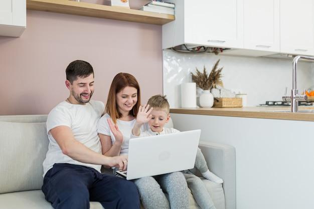 Jong gezin, man, vrouw en twee jonge zonen, die thuis in de keuken zitten en via een videoverbinding met familie communiceren, met behulp van laptop