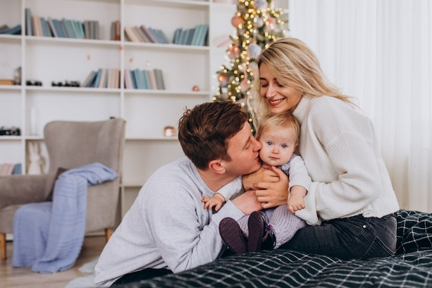 Jong gezin met baby meisje zitten door kerstboom