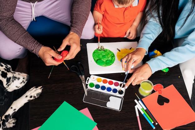 Jong gezin met een hond doet thuis creatief werk, schilderen en beeldhouwen met plasticine