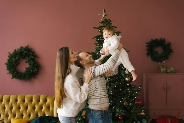 Jong gezin met een klein kind in de buurt van de kerstboom