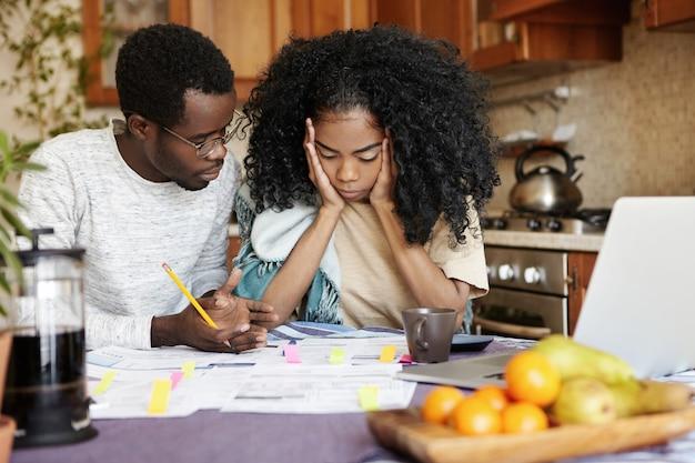 Jong gezin met financieel probleem: gefrustreerde vrouw houdt handen op haar wangen, kijkt wanhopig naar papieren op tafel, kan niet tegen stress, haar man zegt dat alles goed komt