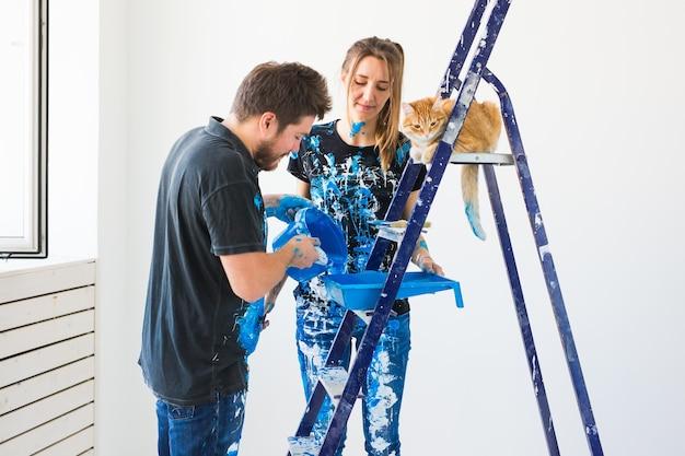 Jong gezin met kat doet reparatie en schilderen muren samen en lachen.