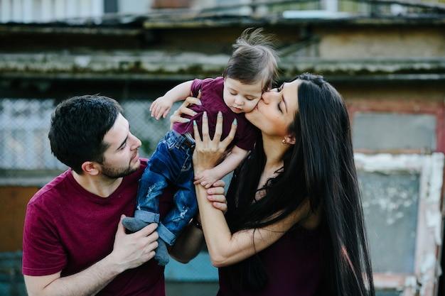 Jong gezin met kind poseren op een verlaten gebouw