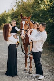 Jong gezin met kinderen plezier met paard in het bos