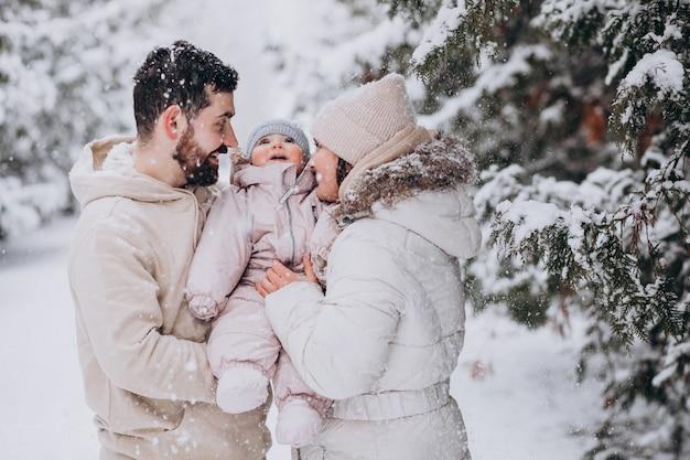 Jong gezin met kleine dochter in een winter bos vol met sneeuw
