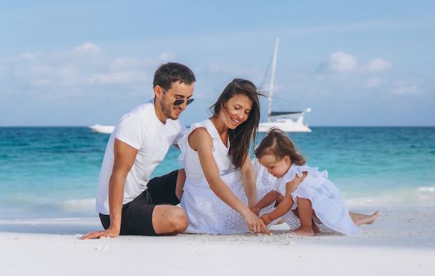Jong gezin met kleine dochter op vakantie aan zee