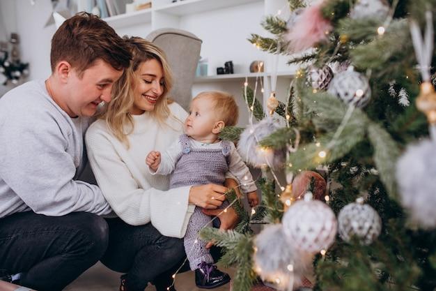 Jong gezin met kleine dochter opknoping speelgoed op kerstboom