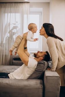 Jong gezin met peuter babydochter zittend op coach thuis