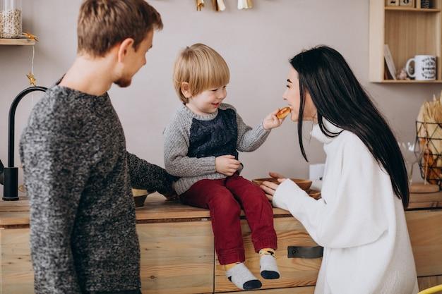 Jong gezin met zoontje op keuken op kerstmis