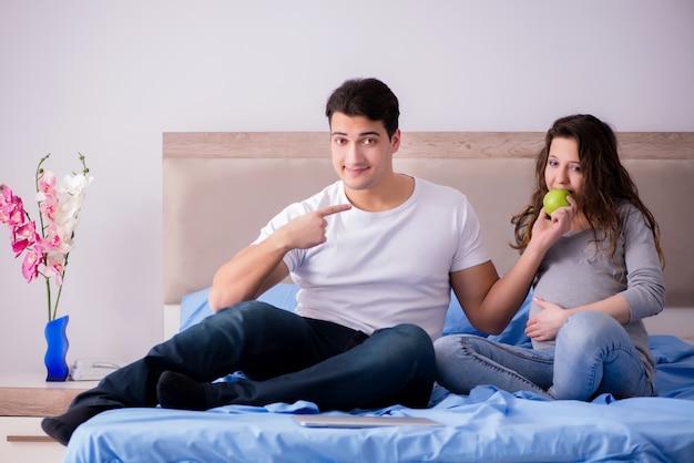 Jong gezin met zwangere vrouw die baby in bed verwacht