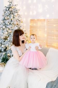 Jong gezin, moeder met babymeisje, zittend op de bank, op de achtergrond van de kerstboom