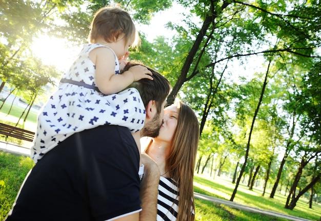 Jong gezin op de wandeling. dochtertje zit op de schouders van de vader.