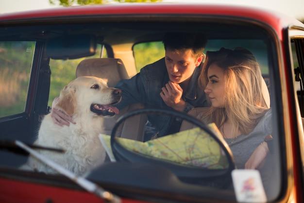 Jong gezin op een road trip met hun hond
