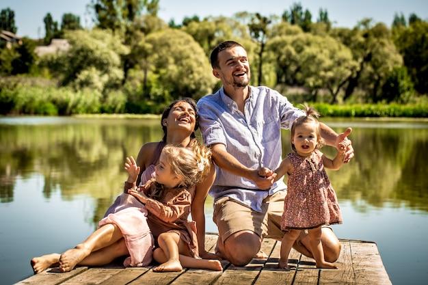 Jong gezin op pier in de buurt van het meer