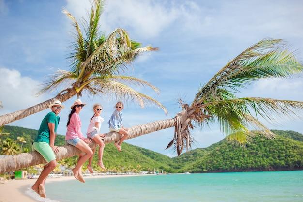 Jong gezin op vakantie heeft veel plezier op palmboom