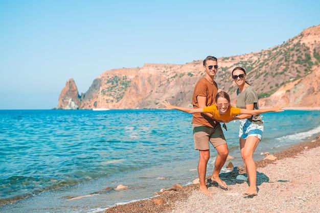 Jong gezin op wit strand tijdens zomervakantie