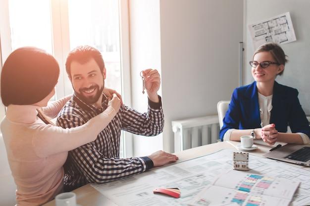 Jong gezin paar aankoop onroerend goed onroerend goed. agent die overleg geeft aan man en vrouw. ondertekening contract voor het kopen van een huis of flat of appartementen. sleutels geven aan een paar klanten.