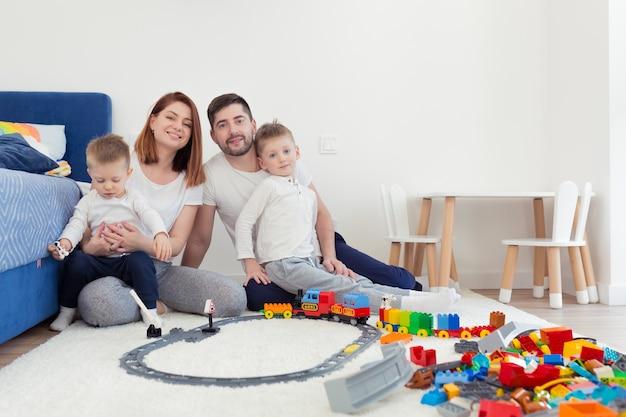 Jong gezin, pappa en mamma met twee jonge zonen, spelen met speelgoed in de kinderkamer, gelukkige familie samen plezier