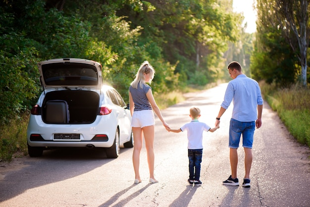 Jong gezin reist met de auto. vader, moeder en zoontje nemen een pauze van autorijden en lopen.
