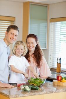 Jong gezin salade voorbereiden