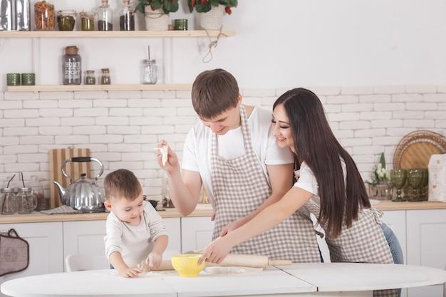 Jong gezin samen koken. man, vrouw en hun kleine baby op de keuken. familie die het deeg met bloem kneedt. mensen koken het diner of ontbijt.
