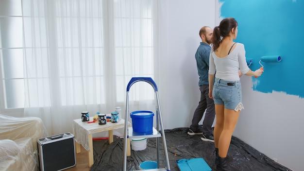Jong gezin schilderen appartement muur tijdens het opknappen met rolborstel. appartement herinrichting en woningbouw tijdens renovatie en verbetering. reparatie en decoreren.