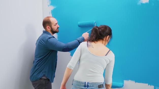 Jong gezin schilderen appartement muur tijdens huisreparatie. decoratie, constructie, make-over. woondecoratie en renovatie in een gezellig appartement, reparatie en make-over