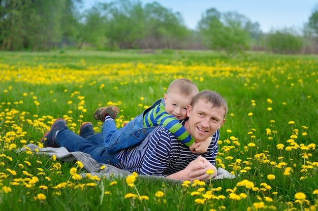 Jong gezin - vader en zoon op de weide met gele bloemen in het voorjaar