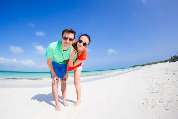 Jong gezin van twee op het witte strand heeft veel plezier