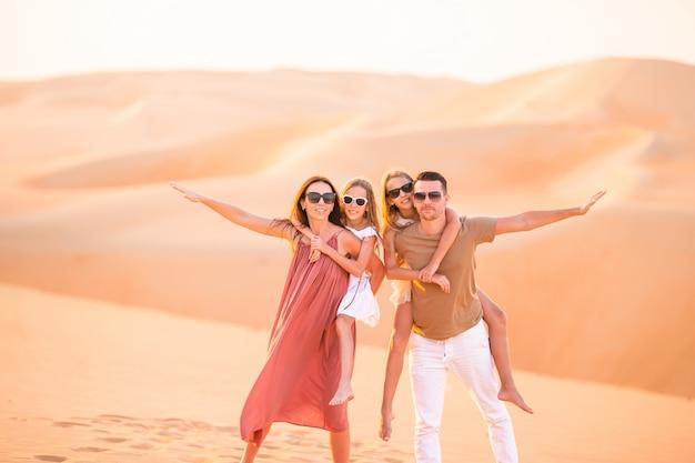 Jong gezin van vier in grote zandwoestijn