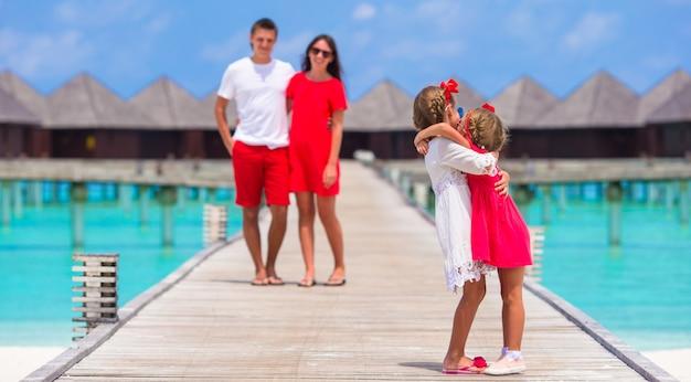 Jong gezin van vier veel plezier op houten steiger tijdens de zomervakantie