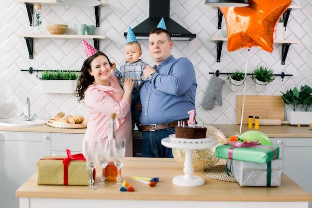 Jong gezin viert de eerste verjaardag van hun kleine babyjongen met een taart, huidige dozen en luchtballonnen. verjaardagsfeestje concept, familie en kind