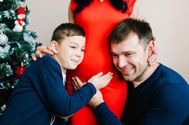 Jong gezin viert kerstmis thuis in de buurt van de kerstboom gelukkige moeder, vader en zoon genieten van