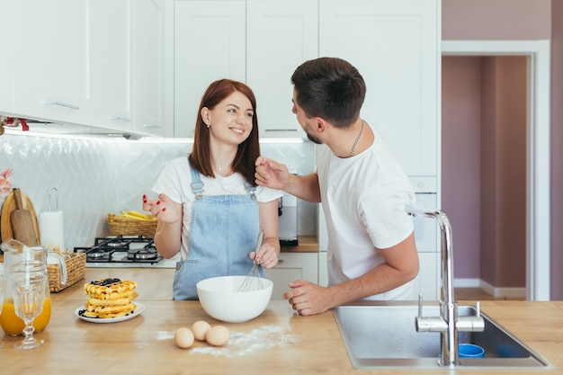 Jong gezin voorbereiding ontbijt samen, echtgenoot en gelukkige vrouw