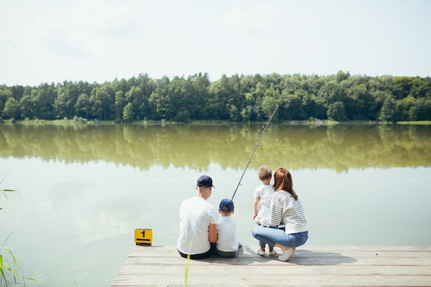 Jong gezin, vrouw man en twee kleine kinderen vissen op het meer, man en vrouw brengen samen een gelukkig weekend door