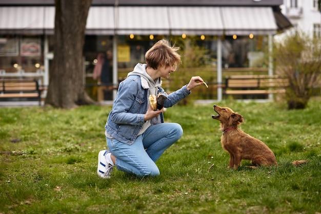 Jong gezin wandelen met een hond door de straten van de stad