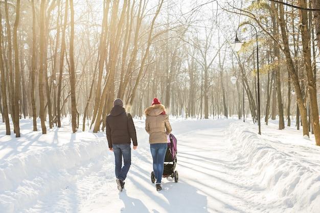 Jong gezin wandelen met kinderwagen in park.