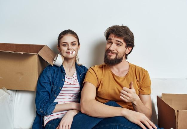 Jong gezin zittend op bankdozen met verhuisdozen
