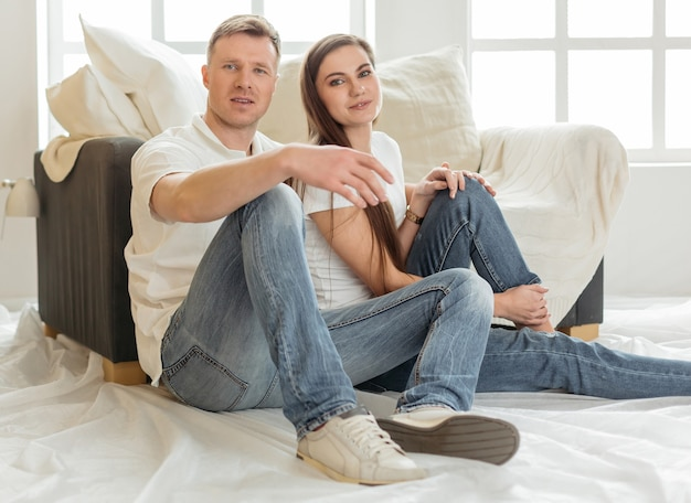 Jong gezin zittend op de vloer in de nieuwe woonkamer. foto met kopieerruimte