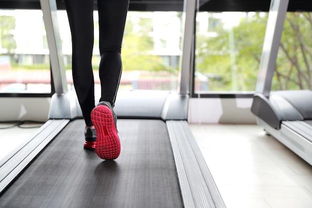 Jong gezond en sportief meisje die of op oefeningsmachine lopen lopen in gymnastiek