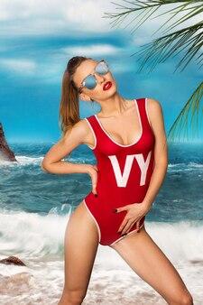 Jong glamourmeisje in rood lichaamszwempak bij het strand